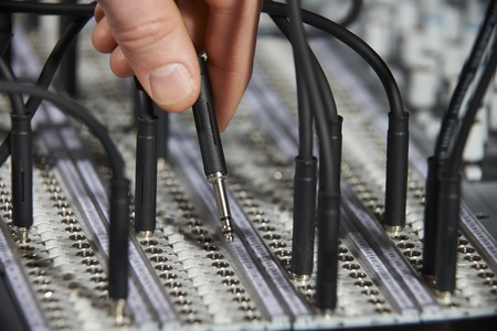 patch panel: Hand Plugging Cable Into Recording Studio Patch Panel Stock Photo
