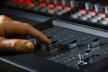 fader: Close Up Of Recording Engineer Pushing Fader In Studio