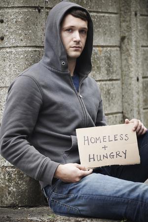 hombre pobre: Hombre sin hogar que pide en la calle joven