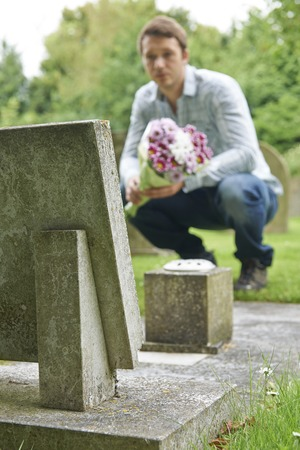 bereavement: Man Laying Flowers On Grave