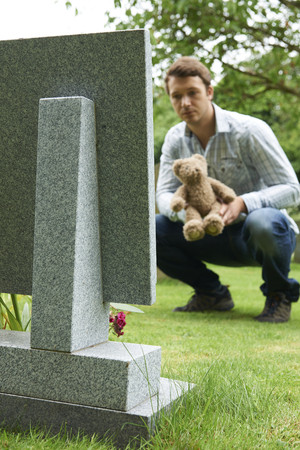 grave: Father Placing Teddy Bear On Childs Grave In Cemetery Stock Photo
