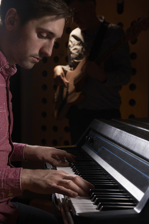 bass guitar: Musicians Playing Electric Piano And Bass Guitar In Recording St