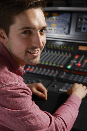 music production: Engineer Working At Mixing Desk In Recording Studio
