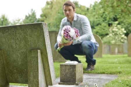 bereavement: Man Placing Flowers By Headstone In Cemetery