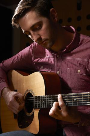 guitarra acustica: Hombre tocando la guitarra acústica En Estudio de grabación