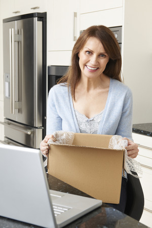 purchase: Woman Unpacking Online Purchase At Home