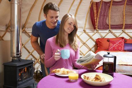 wood burner: Couple Enjoying Camping Holiday In Traditional Yurt