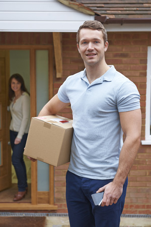 courier: Courier Delivering Package To Domestic House