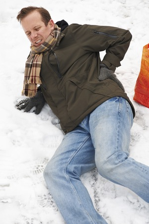 slippery: Man Slipping Over In Snowy Street Stock Photo