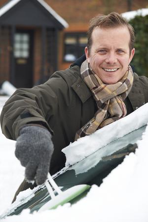 scraping: Man Scraping Snow From Car Windscreen