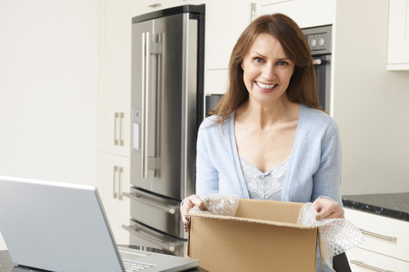 unwrapping: Woman Unpacking Online Purchase At Home