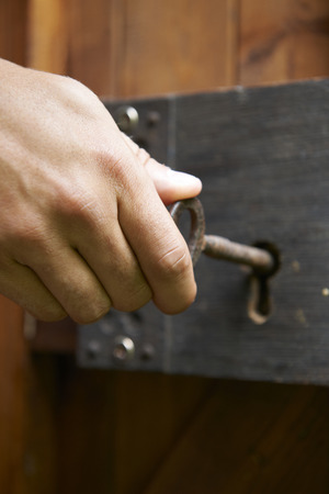 old fashioned: Hand Turning Key In Old Fashioned Lock Stock Photo
