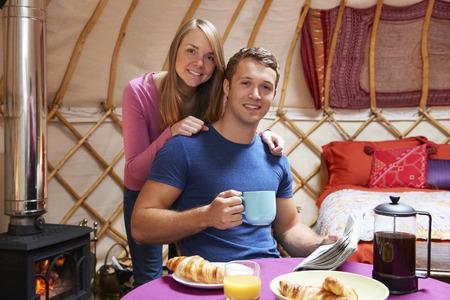 wood burner: Couple Enjoying Breakfast Whilst Camping In Traditional Yurt Stock Photo