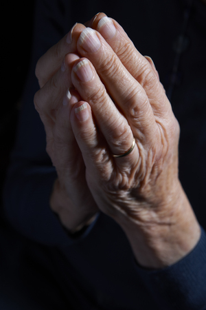 elderly adults: Senior Womans Hands Clasped In Prayer