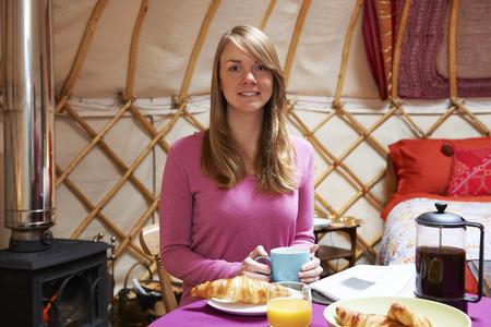 wood burner: Woman Enjoying Breakfast Whilst Camping In Traditional Yurt Stock Photo
