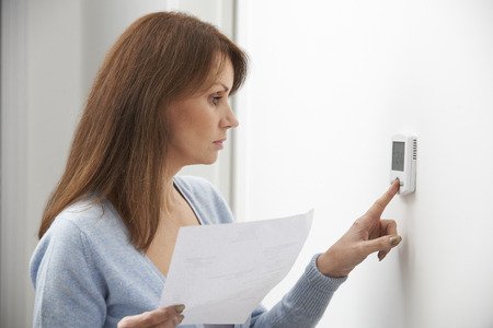copy space: Worried Woman Turning Down Central Heating Thermostat