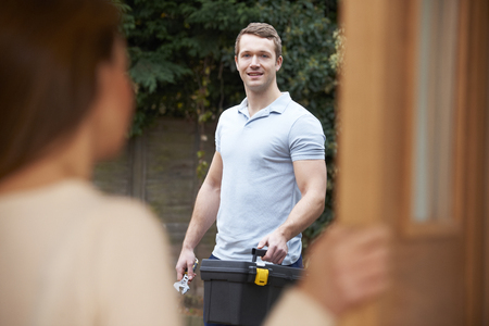door opening: Woman Opening Door To Repairman Stock Photo