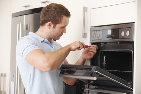 home appliance: Man Repairing Domestic Oven In Kitchen Stock Photo