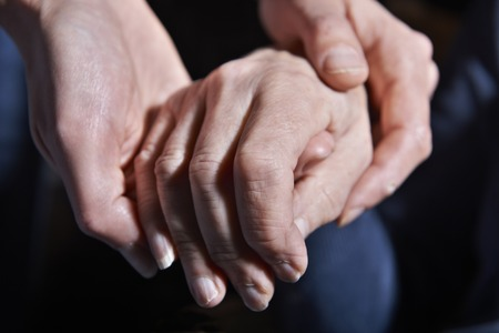 the ageing process: Young Woman Holding Old Womans Hand Against Black Background