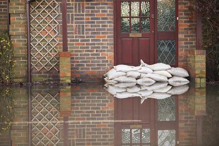 Los sacos de arena en el exterior de la puerta principal de casa inundada Foto de archivo - 49640689