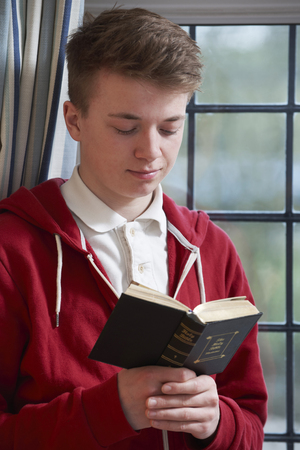religious text: Teenage Boy Reading Bible At Home Stock Photo