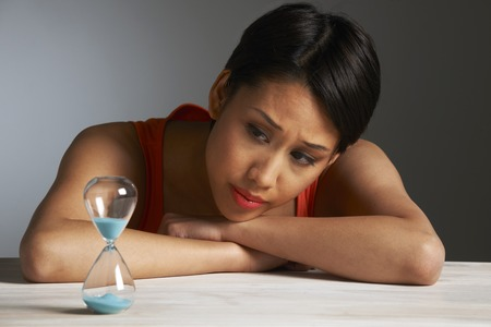 the ageing process: Sad Young Woman Looking At Hourglass Stock Photo