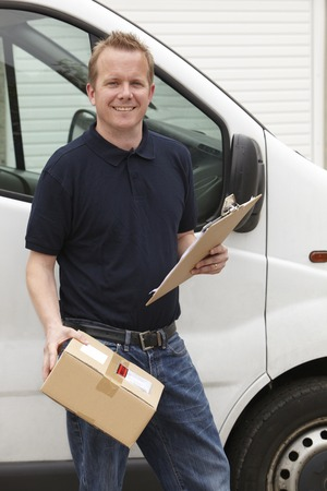 courier: Courier Delivering Package Standing Next To Van Stock Photo