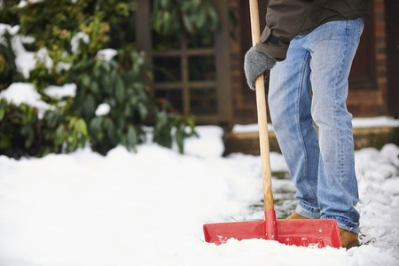 snow house: Man Clearing Snow From Path With Shovel Stock Photo