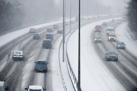 snowstorm: Traffic On Motorway During Snowstorm Stock Photo