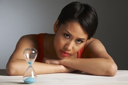 the ageing process: Sad Woman Looking At Hourglass