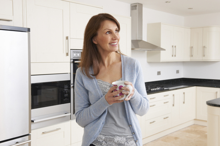 fitted: Woman Standing In New Luxury Fitted Kitchen
