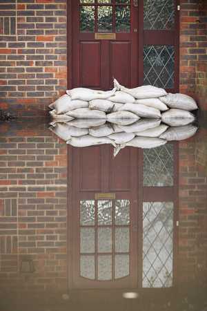 Sandbags Outside Front Door Of Flooded House Archivio Fotografico