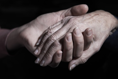 old hand: Young Woman Holding Old Womans Hand Against Black Background