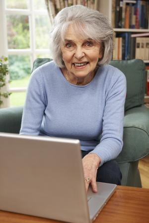 persona de la tercera edad: Mujer Senior con el portátil en casa Foto de archivo