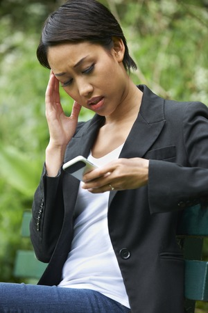 unhappy: Worried Young Woman Reading Text Message