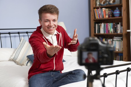 video camera: Teenage Boy Recording Video Of Himself In Bedroom