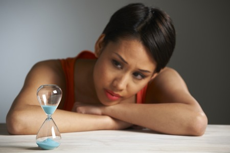 ageing process: Sad Woman Looking At Hourglass