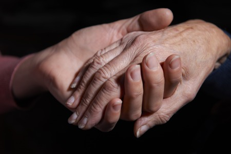 the ageing process: Young Woman Holding Older Womans Hand Stock Photo