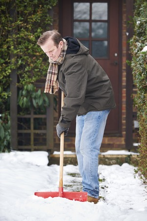 clearing: Man Clearing Snow From Path With Shovel Stock Photo