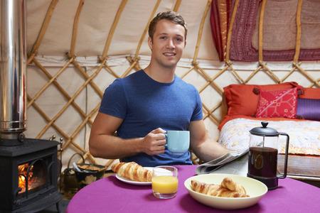 wood burner: Man Enjoying Breakfast Whilst Camping In Traditional Yurt