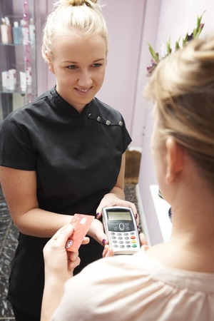 sales assistant: Sales Assistant Accepting Card Payment From Customer Stock Photo