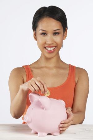 coin bank: Happy Woman Putting Coin Into Savings Bank