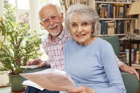 home finances: Happy Senior Couple Reviewing Finances At Home
