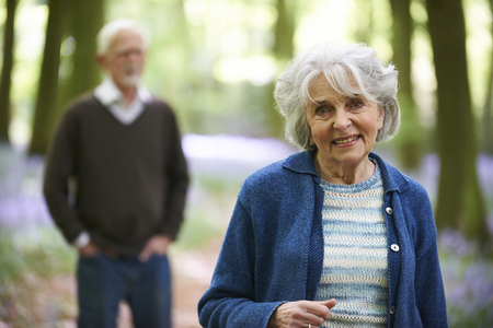 bluebell woods: Senior Couple Walking Through Bluebell Woods Stock Photo