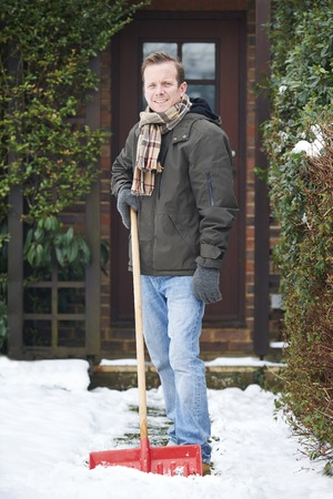snow clearing: Man Clearing Snow Covered Path Outside Home Stock Photo