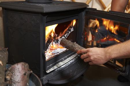 estufa: Hombre que pone inicio sesión en la estufa de leña ardiente