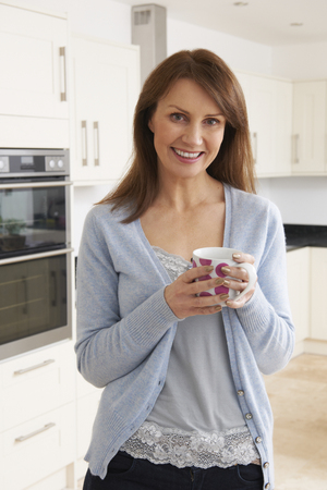 women coffee: Woman Standing In New Luxury Fitted Kitchen