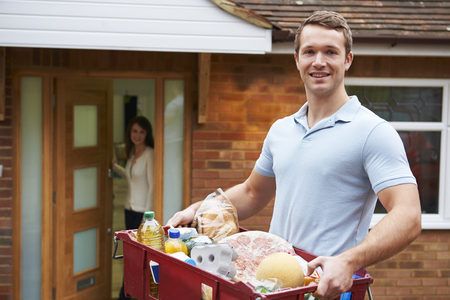man carrying woman: Man Delivering Online Grocery Order