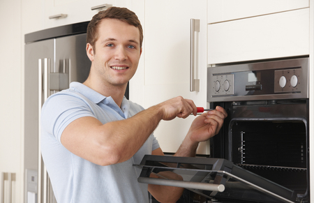 Engineer Reapiring Domestic Oven In Kitchen Stock Photo