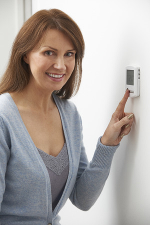 home heating: Smiling Woman Adjusting Thermostat On Home Heating System